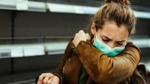 Woman with COVID mask coughing